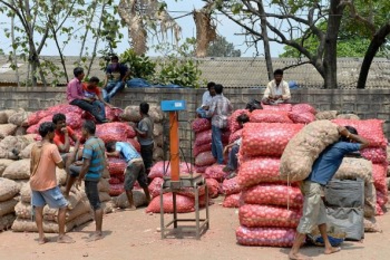 Indian labourers go about their business around sacks of onions at the APMC yard in Bangalore. (Manjunath Kiran/AFP/Getty Images)