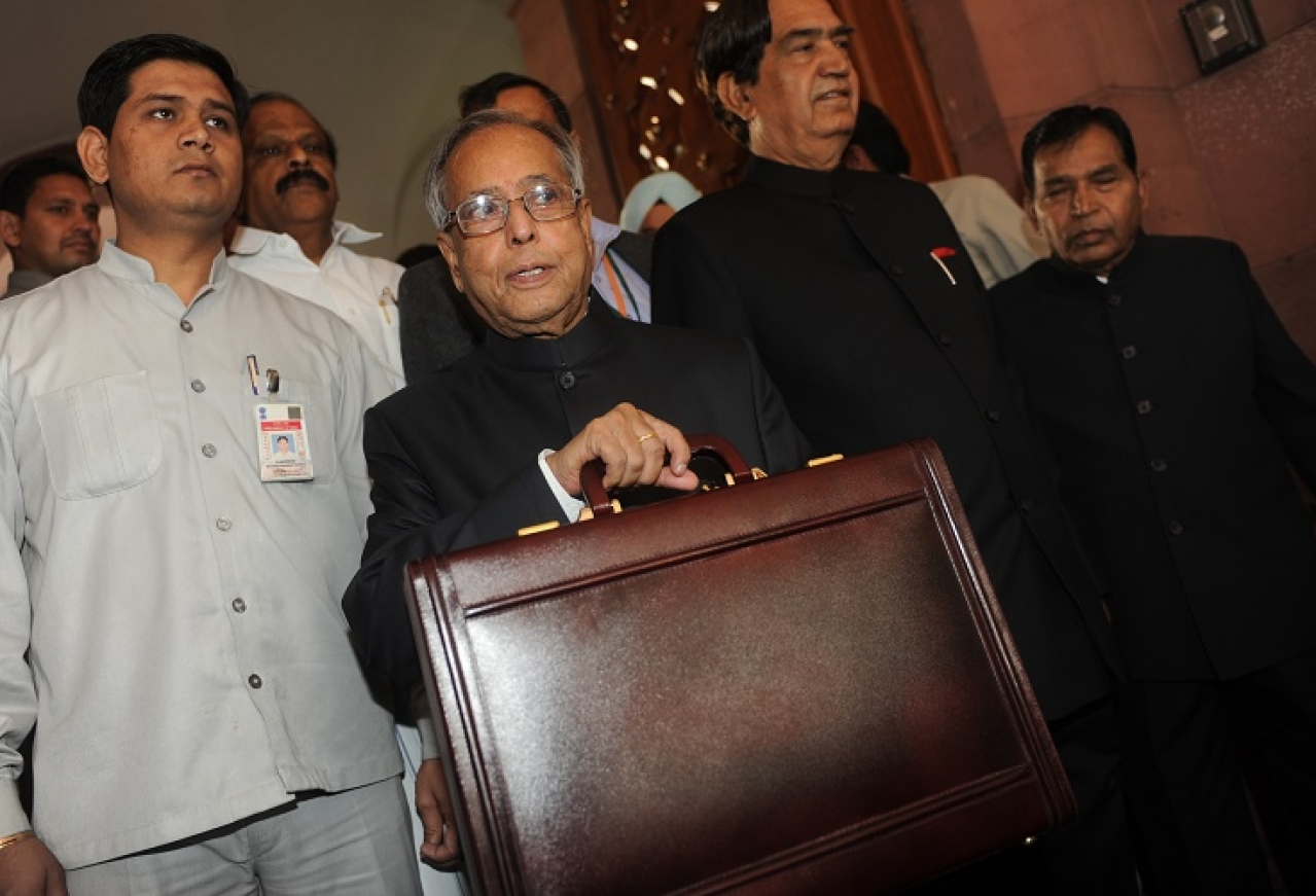 Indian finance minister Pranab Mukherjee (C) poses for the media in parliament prior to presenting the national budget in New Delhi on March 16, 2012.  India's government was due to deliver its budget as an acrimonious split in its ranks over hiking rail fares highlighted the increasingly dysfunctional nature of the ruling coalition. The Congress-led administration, already battered by a string of graft scandals, is under financial market pressure to cut public spending and rein in a ballooning deficit at the same time as spurring slowing growth. AFP PHOTO/ Raveendran (Photo credit should read RAVEENDRAN/AFP/Getty Images)