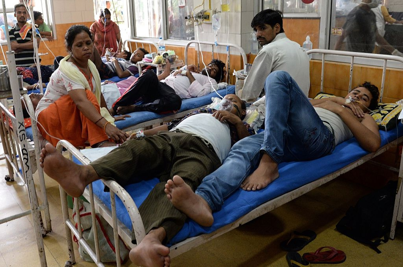 Indian patients share a bed in a dengue ward of Hindu Rao hospital in New Delhi. Photo credit: PRAKASH SINGH/AFP/GettyImages