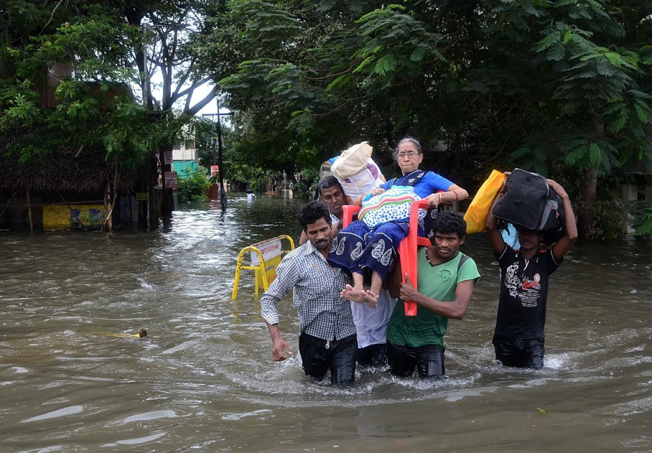 Indian men carry an elderly woman on a flooded street following heavy rain in Chennai. Photo credit:  STR/AFP/GettyImages