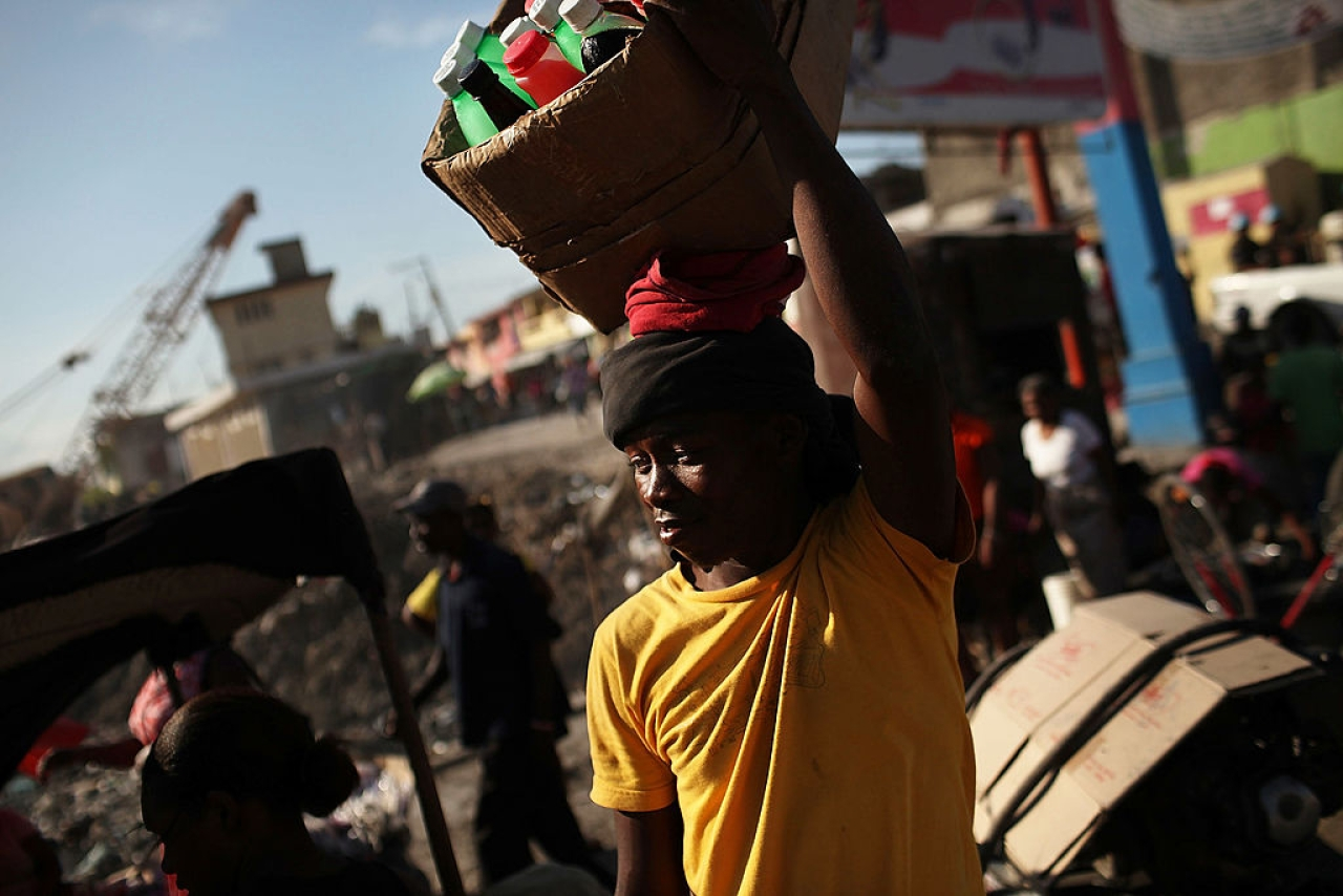 A man walks with merchandise he is trying to sell in Port-au-Prince, Haiti.  Photo credit: Spencer Platt/GettyImages