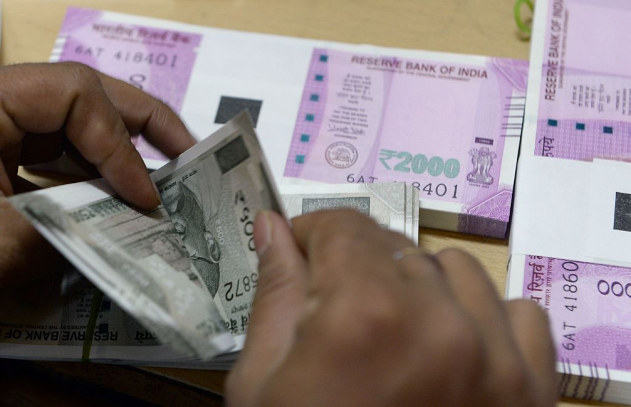 A bank staff member counts Indian 500 rupee notes to give to customers. (INDRANIL MUKHERJEE/AFP/Getty Images)