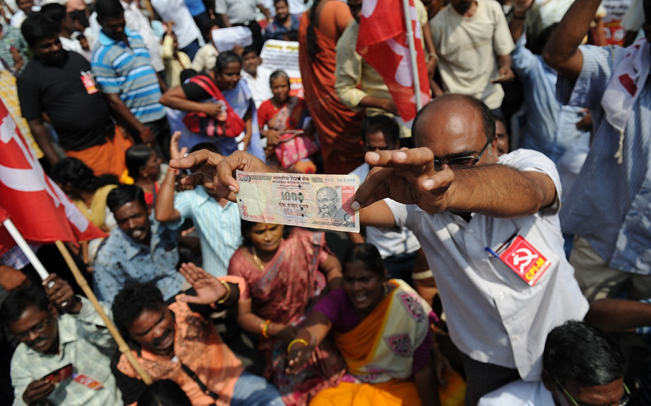 A man displays a Rs 1,000 note at a protest against the withdrawal of high-value banknotes from circulation (ARUN SANKAR/AFP/Getty Images)