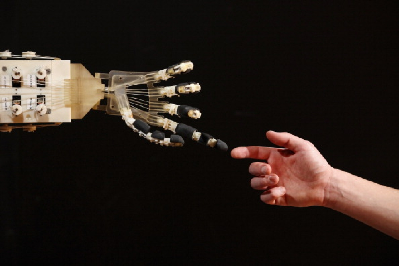 Robotics student Gildo Andreoni interacts with a Dexmart robotic hand built at the University of Bologna in the Robotville exhibition in London, England. (Oli Scarff/Getty Images)