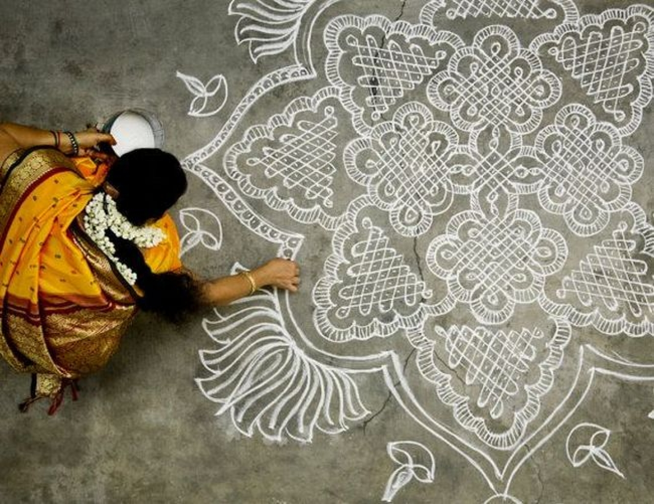 A woman draws a kolam (rangoli) for the New Year