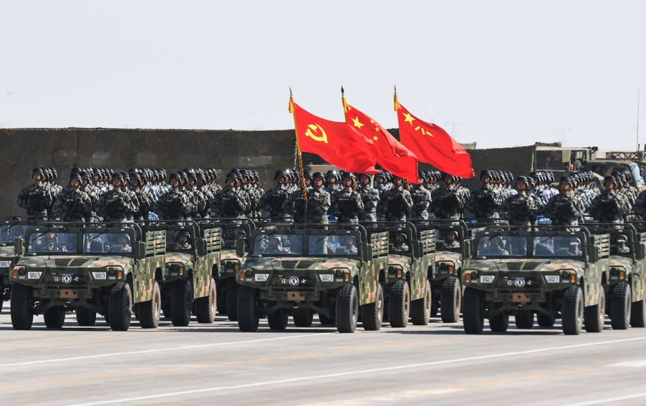 Chinese soldiers carry the flags of (L to R) the Communist Party, the state, and the People's Liberation Army during a military parade at the Zhurihe training base in China's northern Inner Mongolia region on July 30, 2017. (STR/AFP/Getty Images)
