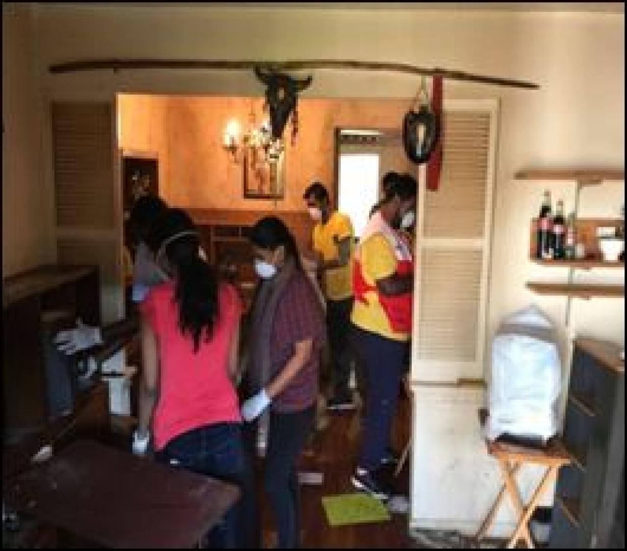 Volunteers clean up debris at homes.