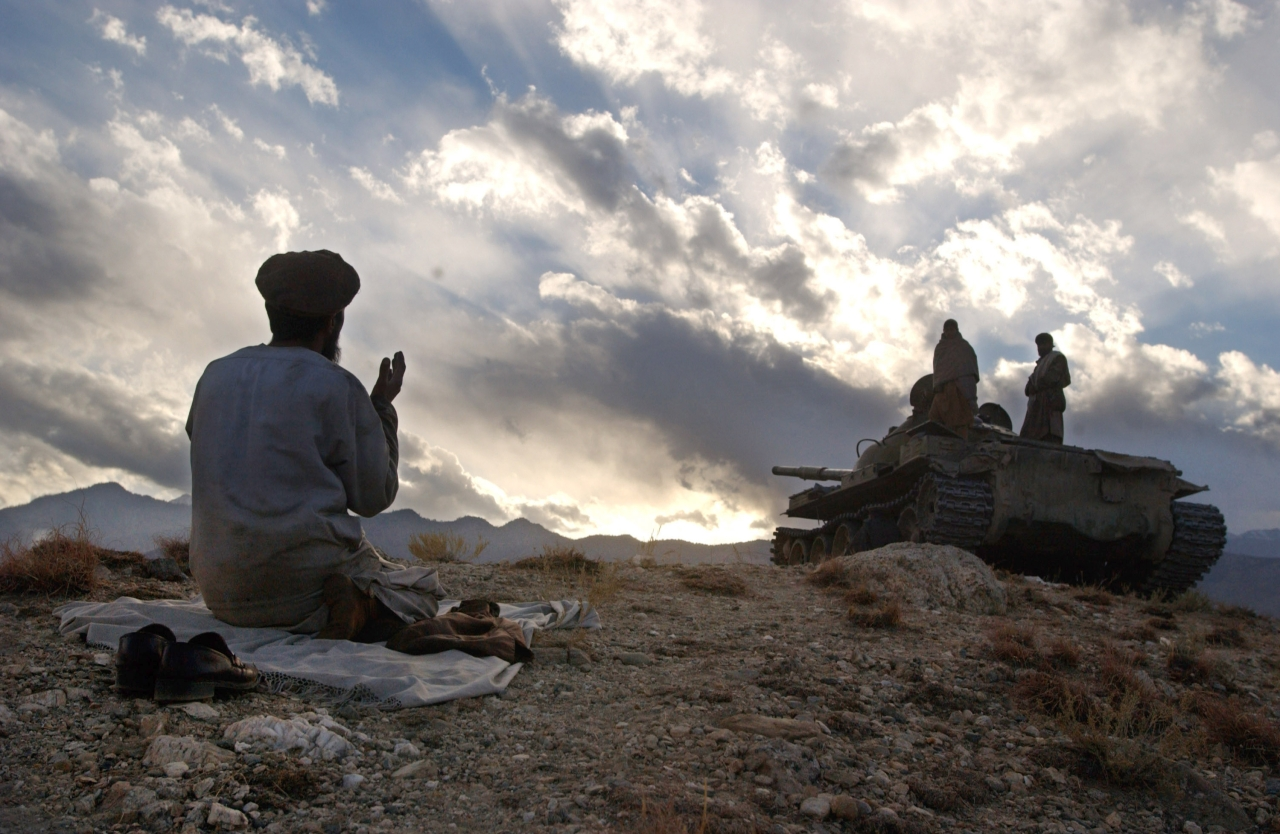 An anti-Taliban soldier  prays near a tank on the hills overlooking the Tora  Bora. (Photo by Chris Hondros/Getty Images)