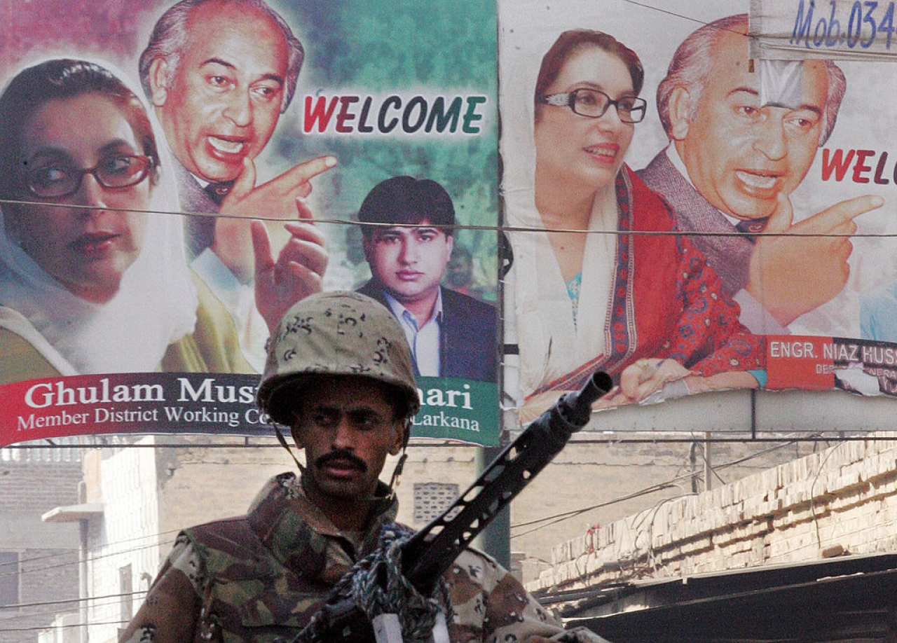 A Pakistani paramilitary soldier stands guard next to posters of slain former Pakistani premier Benazir Bhutto and her father Zulfiqar Ali Bhutto in Larkana. (AAMIR QURESHI/AFP/Getty Images)