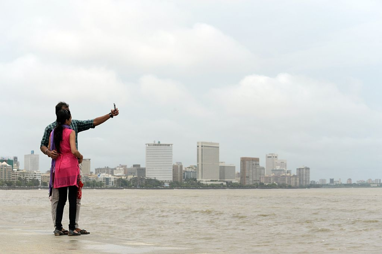 A young Indian couple take a 'selfie' on Marine Drive promenade in Mumbai. (INDRANIL MUKHERJEE/AFP/Getty Images)