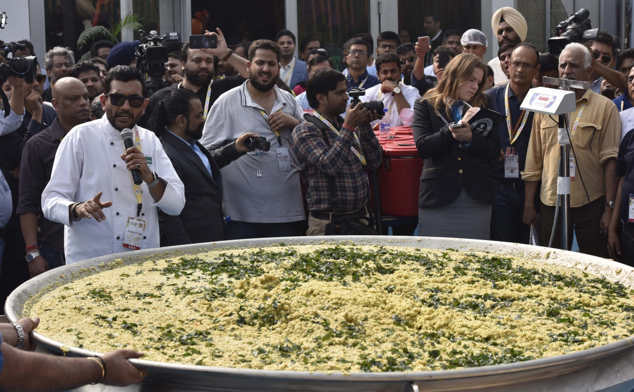 A team of nearly two dozen people cooked khichdi on 4 November in New Delhi in an attempt to enter Guinness World Records at World Food India fair. (Sonu Mehta/Hindustan Times via GettyImages)