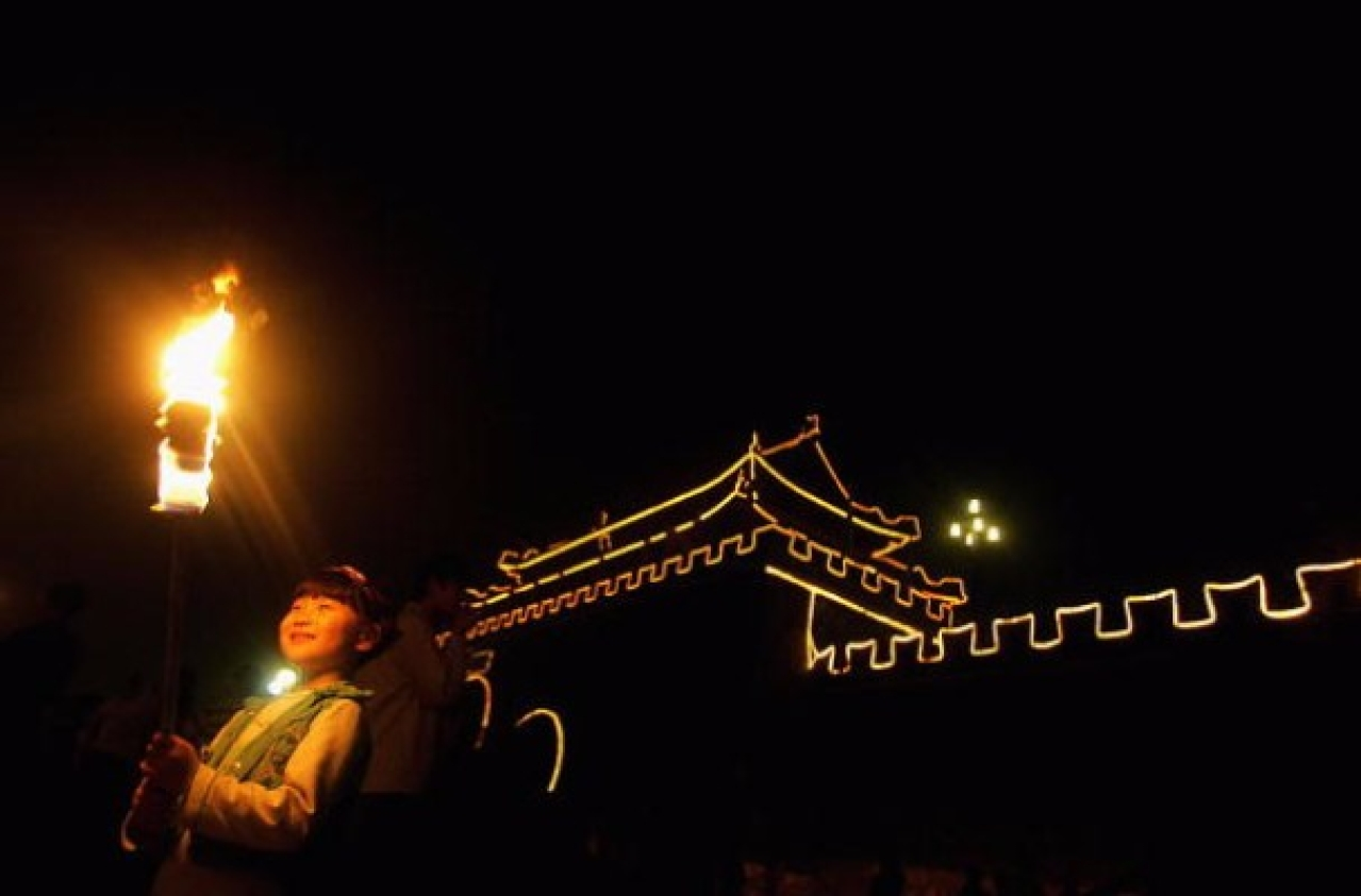A girl holds a torch during an event to mark the Mid-Autumn Festival beside an ancient city wall in  2006 in Shouxian County of Anhui Province, China. (China Photos/Getty Images)