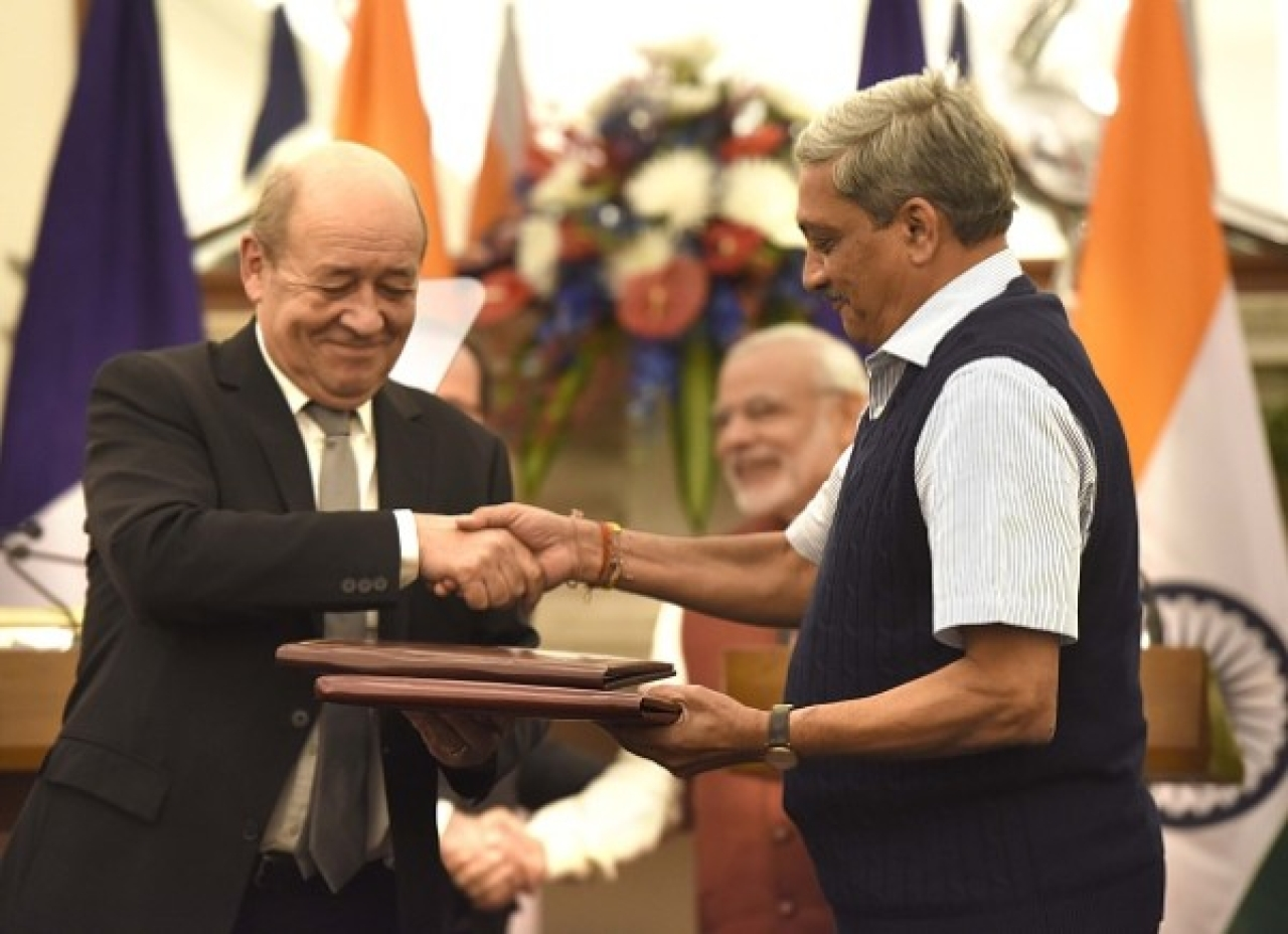 Former defence minister Manohar Parrikar and his French counterpart Jean-Yves Le Drian exchange the files of agreements on the buying of Rafale fighter jets. (Arvind Yadav/Hindustan Times via Getty Images)