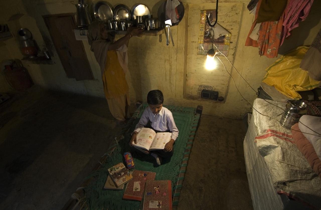 A boy studies under an electric lightbulb in Haryana (Priyanka Parashar/Mint via Getty Images)