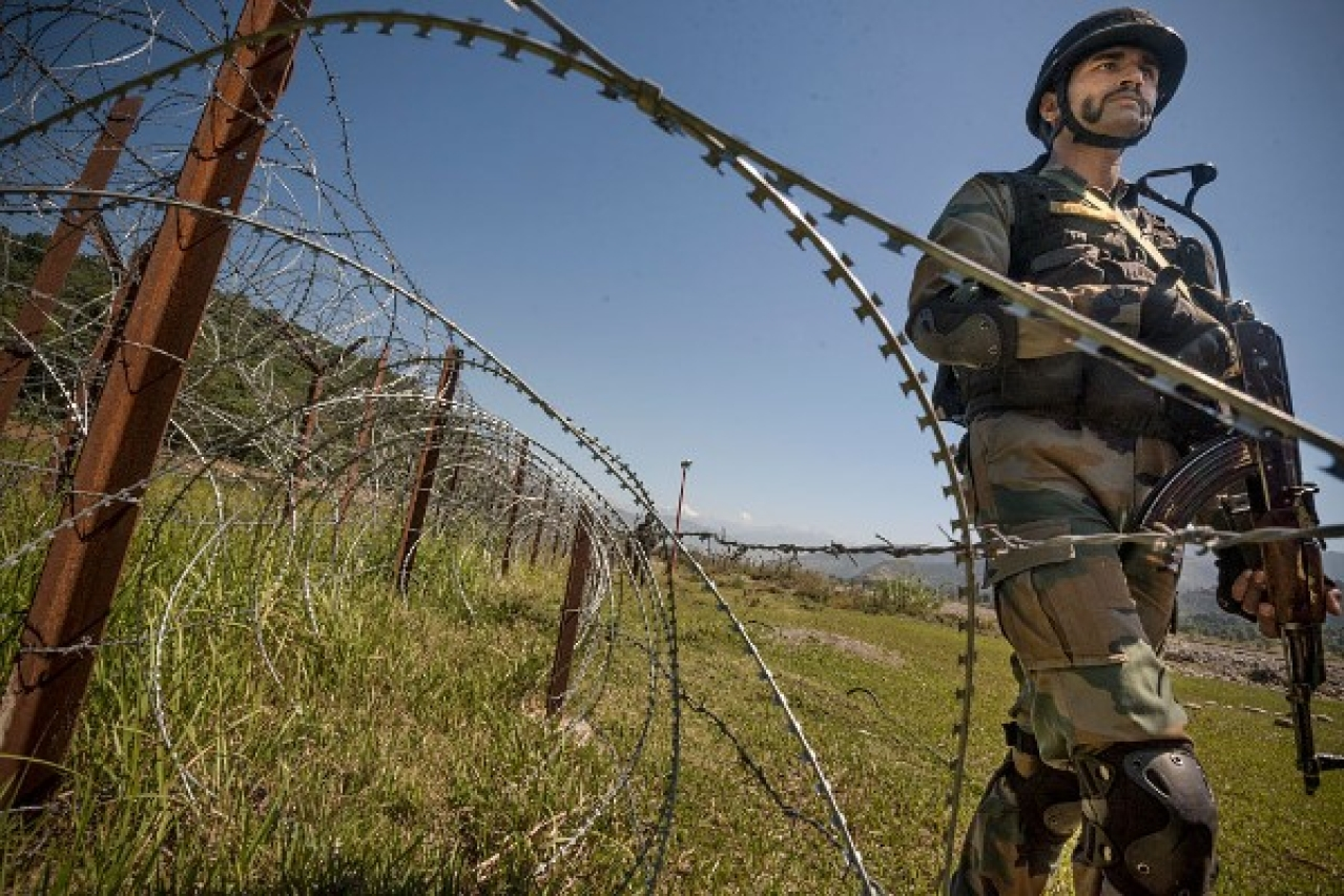 An Indian Army soldier patrols on the fence near the India-Pakistan LOC in Chakan-da-Bagh area near Poonch. (Gurinder Osan/Hindustan Times via Getty Images)