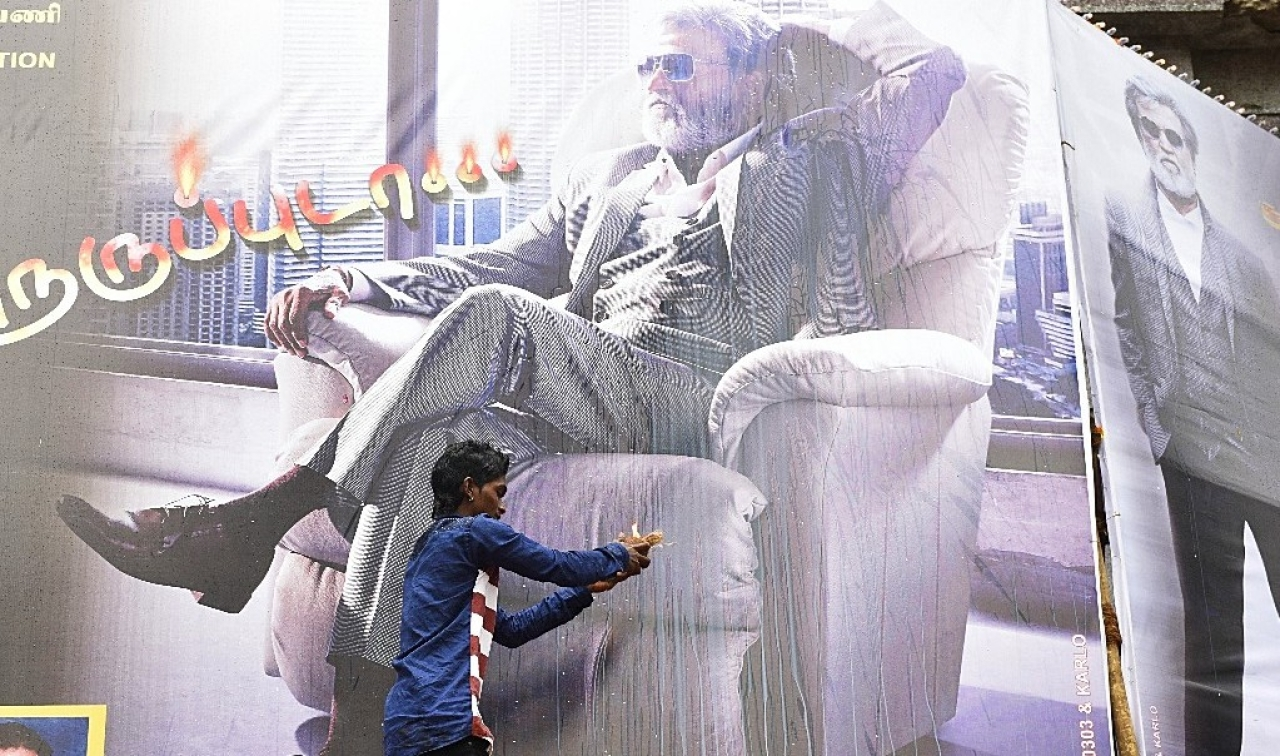 A Rajinikanth fan performs aarti in front of his movie hoarding in Mumbai. (Arijit Sen/Hindustan Times via GettyImages)