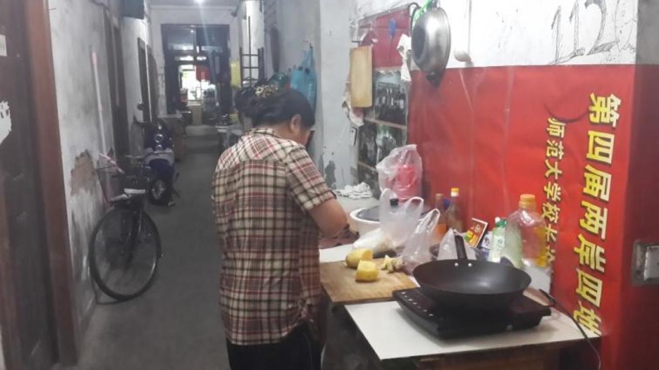 "Ayi preparing dinner in the ""open-air kitchen""."