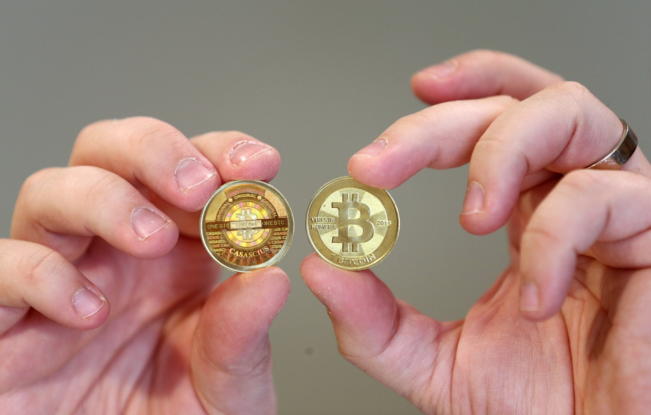 A software engineer shows the front and backa physical Bitcoin he minted in his shop in Sandy, Utah, US.  (George Frey/GettyImages)