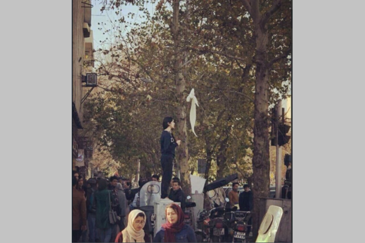 A woman waves a hijab during protests in Iran. (Twitter)
