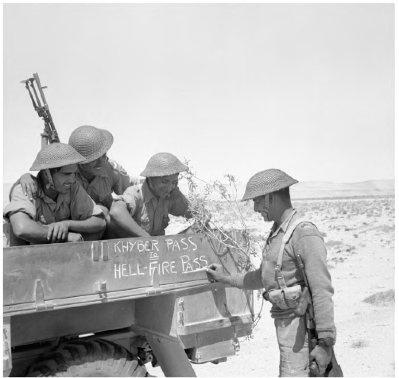 "Soldiers of the Fourth Indian Division decorate the side of their lorry with the words: ""From Khyber Pass to Hellfire Pass"". Hellfire Pass was the  nickname for the strategic Al-Halfaaya Pass in Egypt which the Indians tried to wrest from the Germans."