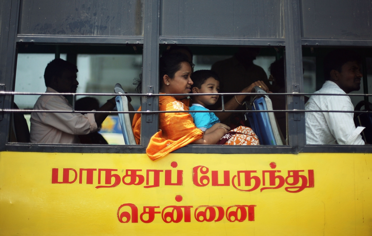 A lady with a young boy on her lap look out the window as they ride the bus. The transport employees have been risking their lives to ensure the communters' safety. (Mark Kolbe/Getty Images)
