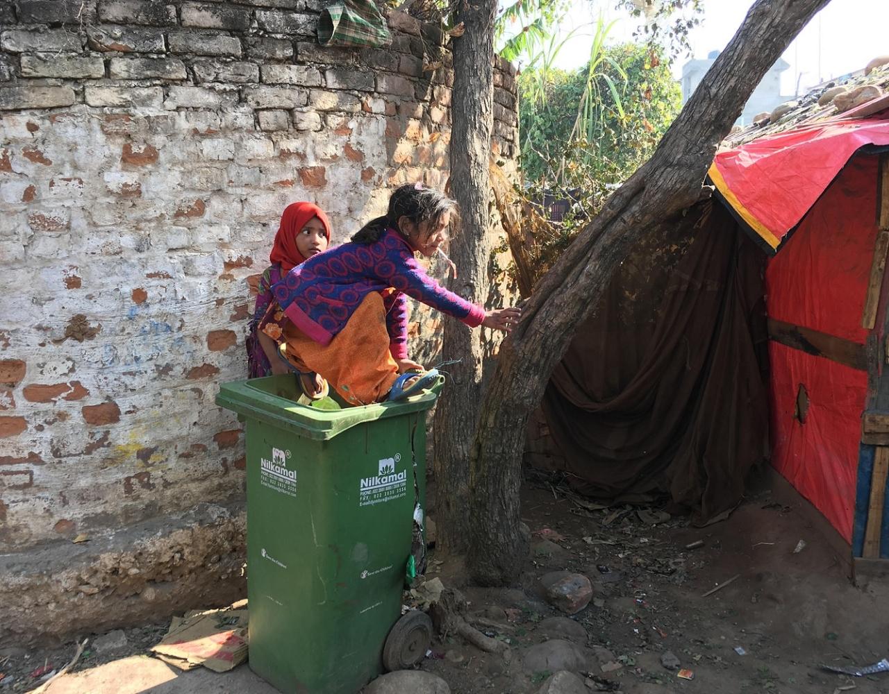 A girl plays with trash at a Rohingya camp in Bhatindi's Kiryani Talab