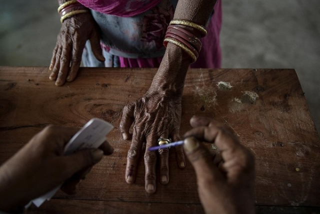 An Indian woman has her finger inked by an election worker before voting. (Kevin Frayer/Getty Images)
