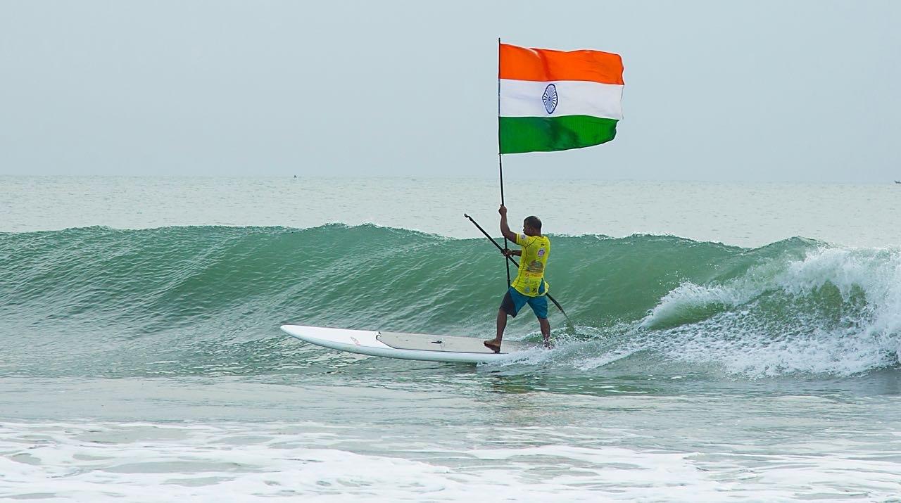 Murthy Megavan surfs holding the national flag