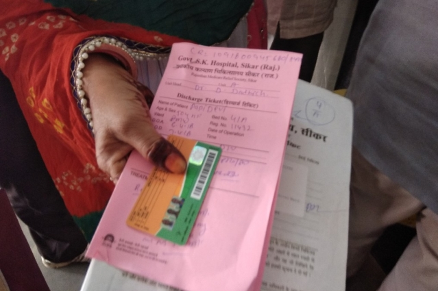 Jaitun Bano holding Pappi Bano's Bhamashah Card and discharge and prescription papers.
