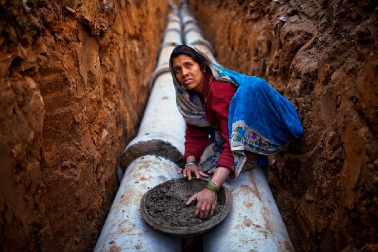 An Indian woman works at a construction project in front of the Jawaharlal Nehru Stadium in New Delhi. (Daniel Berehulak/Getty Images)