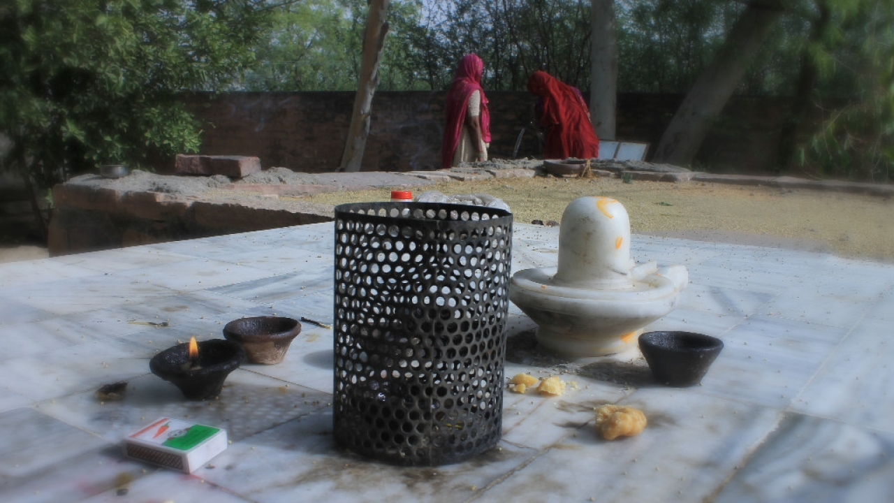 Women at a temple draw water from the well. They would have the first sip after offering it to the trees.