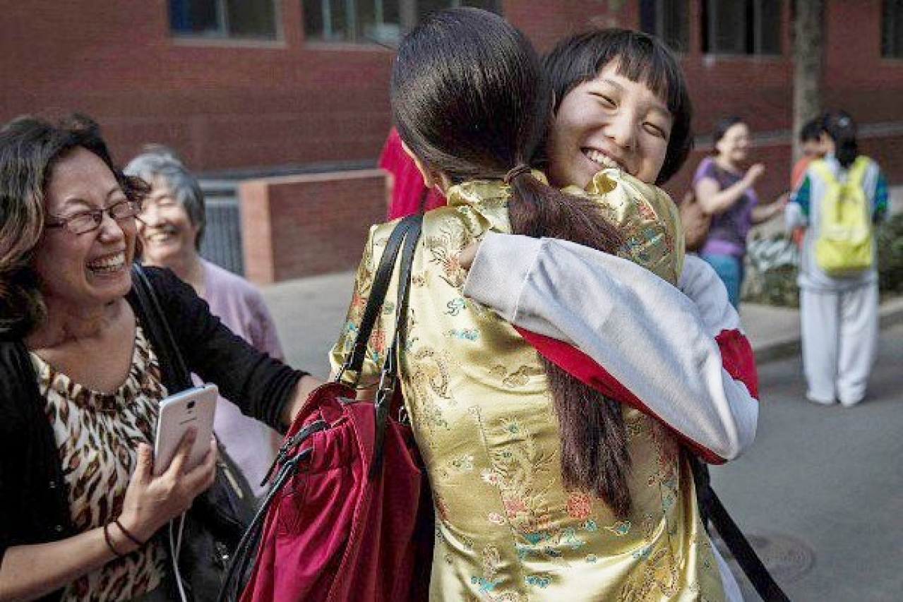 A Chinese student is hugged by relatives after completing the Gaokao at the Beijing Renmin University Affiliated High School, in Beijing, China. (Kevin Frayer/Getty Images)