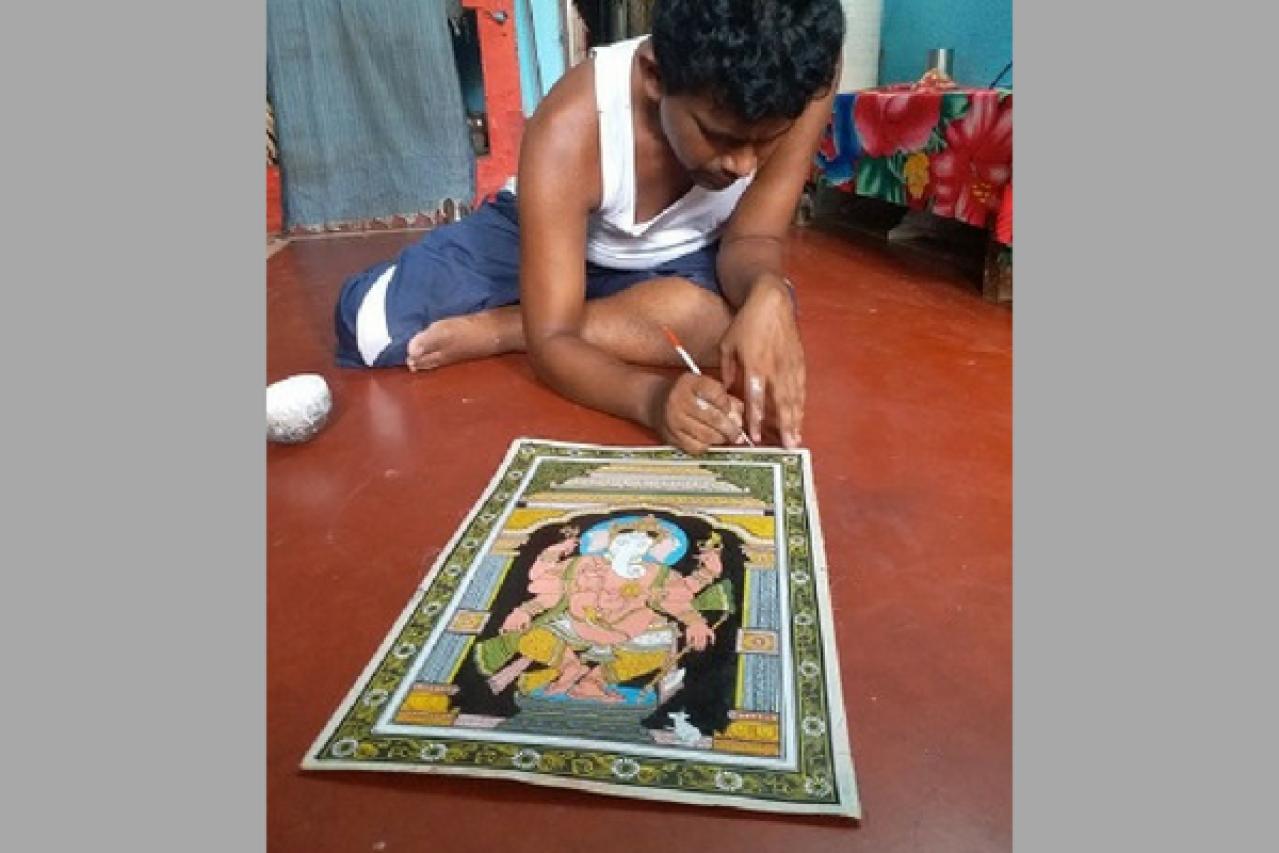 Artist Narayan Mahapatra paints a Ganesha on a canvas