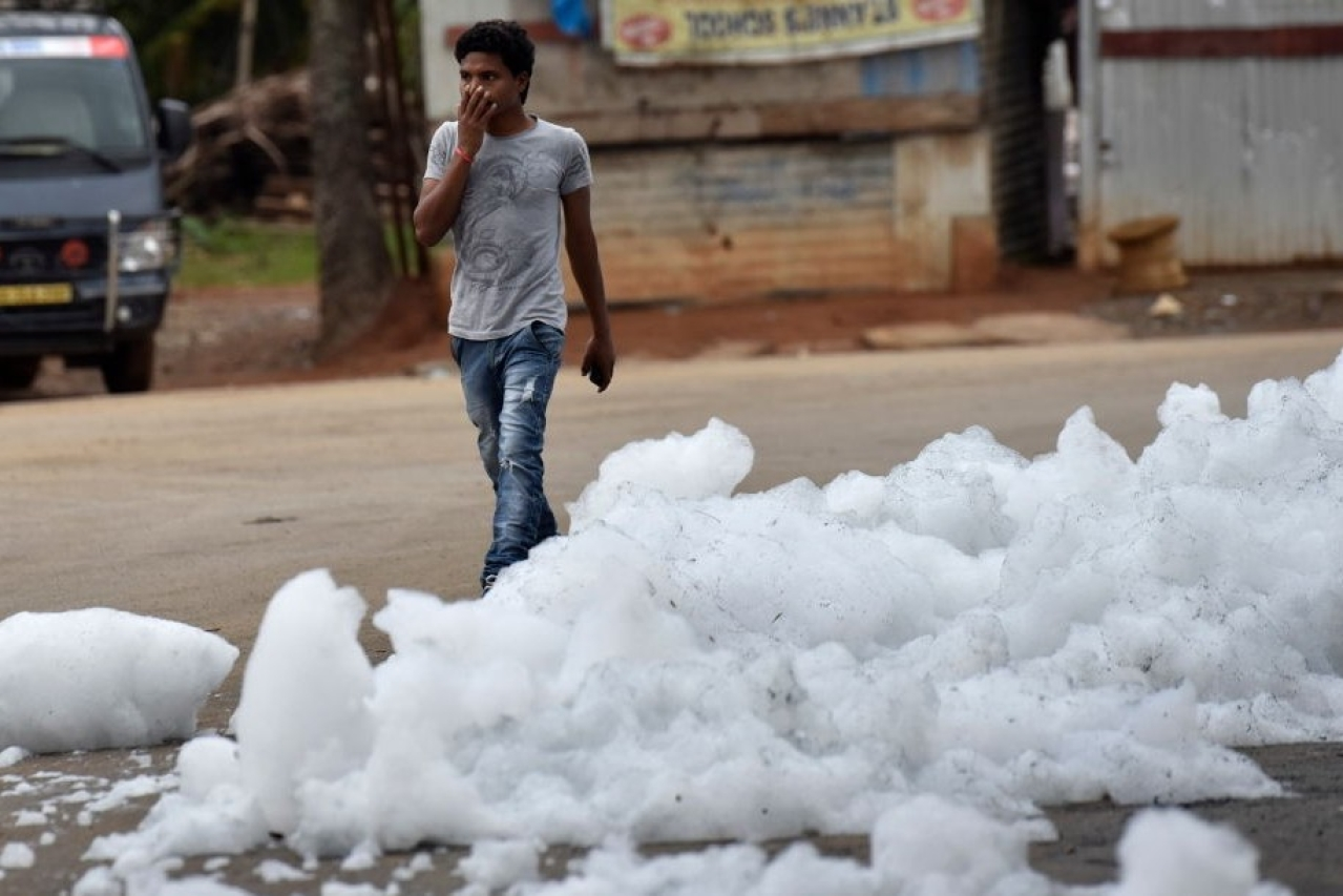 A youngster walks through  the flying froth from the polluted Bellandur Lake in Bengaluru. (Arijit Sen/Hindustan Times via GettyImages)