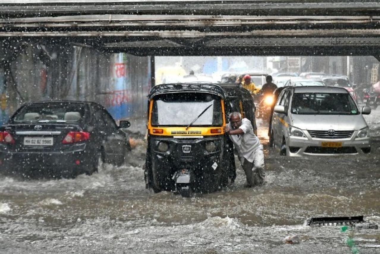 A man pushes his vehicle as it rains at Andheri Subway in Mumbai. (Shashi S Kashyap/Hindustan Times via Getty Images)