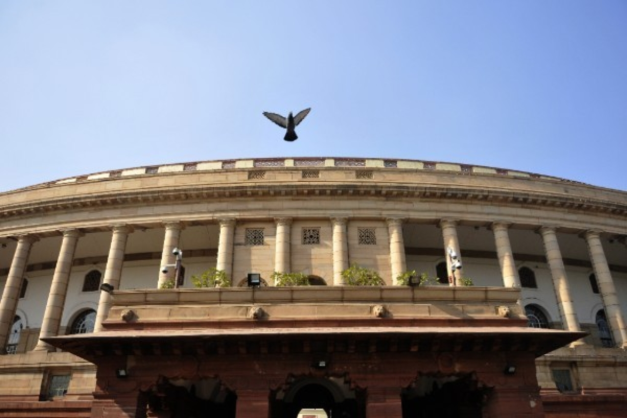 A pigeon flies over the Parliament building during the winter session in December 2015 in New Delhi. (Vipin Kumar/Hindustan Times via Getty Images)