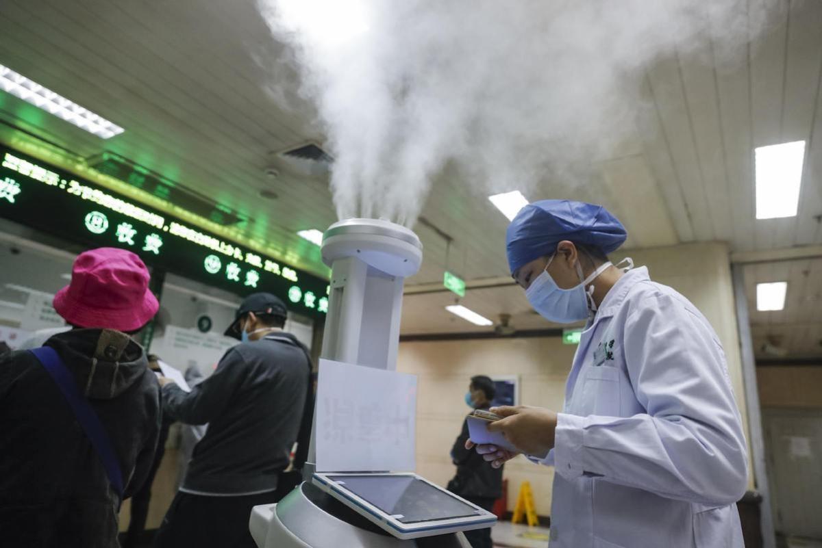 स्वास्थ्यकर्मी अस्पताल में टैबलेट के जरीये कीटाणुनाशक रोबोट को नियंत्रित करते हुए.