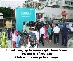 Crowd lining up to receive gifts from Croma 'Moments of Joy van'