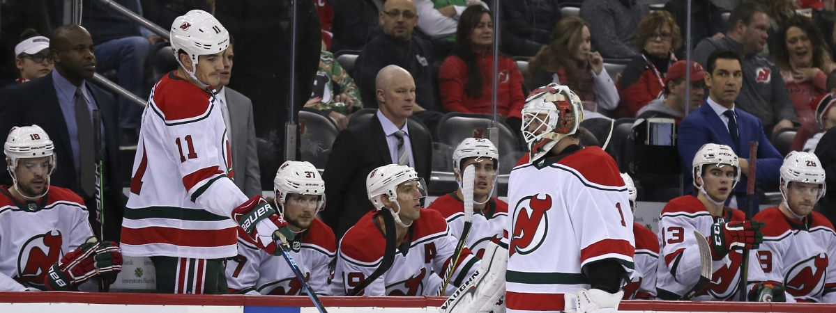 New Jersey Devils goaltender Keith Kinkaid (1) skates past the Devils' Brian Boyle (11) and head coach John Hynes, center (in suit), after being replaced during the second period of an NHL hockey game Sunday, Dec. 23, 2018, in Newark, N.J. (AP Photo/Adam Hunger)