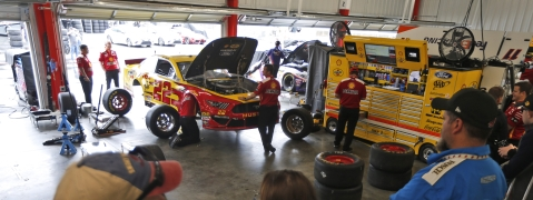 Fans watch the team of Joey Logano as they work on the car in the garage at Richmond Friday (Steve Helber)