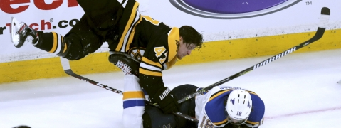 Boston Bruins' Torey Krug, top, checks St. Louis Blues' Robert Thomas to the ice during the third period in Game 1 of the NHL hockey Stanley Cup Final on May 27, 2019.