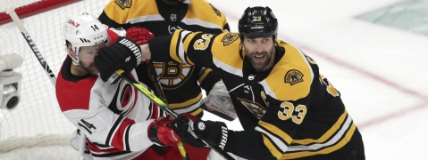 Boston Bruins' Zdeno Chara (33) pushes Carolina Hurricanes' Justin Williams (14) away from Bruins goalie Tuukka Rask during Game 2 of the NHL hockey Stanley Cup Eastern Conference final series on May 12, 2019