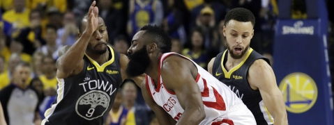 Houston Rockets' James Harden, center, is defended by Golden State Warriors' Andre Iguodala, left, and Stephen Curry in Game 2 of a second-round NBAplayoff series in Oakland, Tuesday, April 30, 2019. (AP Photo/Jeff Chiu)