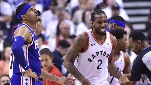 Toronto Raptors forward Kawhi Leonard smiles as Philadelphia 76ers forward Tobias Harris looks at the scoreboard during the first half of Game 5 of the NBA basketball second-round playoff series on May 7, 2019.