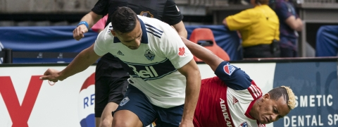 Vancouver Whitecaps' Ali Adnan, left, battles with FC Dallas' Michael Barrios for control of the ball during the first half of an MLS soccer match Saturday, May 25, 2019, in Vancouver, British Columbia. (Richard Lam/The Canadian Press via AP)