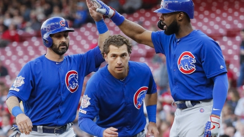 Chicago Cubs' Albert Almora Jr., center, and Daniel Descalso, left, celebrate with Jason Heyward, right, after scoring on a two-run double by Kyle Hendricks off Cincinnati Reds starting pitcher Tanner Roark during the second inning of a baseball game on May 14, 2019.