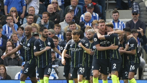 Manchester City's Aymeric Laporte is hugged by teammate Kyle Walker, foreground right, after scoring his side's second goal during the English Premier League soccer match between Brighton and Manchester City at the AMEX Stadium in Brighton, England, Sunday, May 12, 2019. (AP Photo/Frank Augstein)