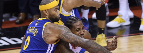 Golden State Warriors' DeMarcus Cousins ties up Toronto Raptors' Kawhi Leonard during the second half of Game 2 of basketball's NBA Finals on June 2, 2019.