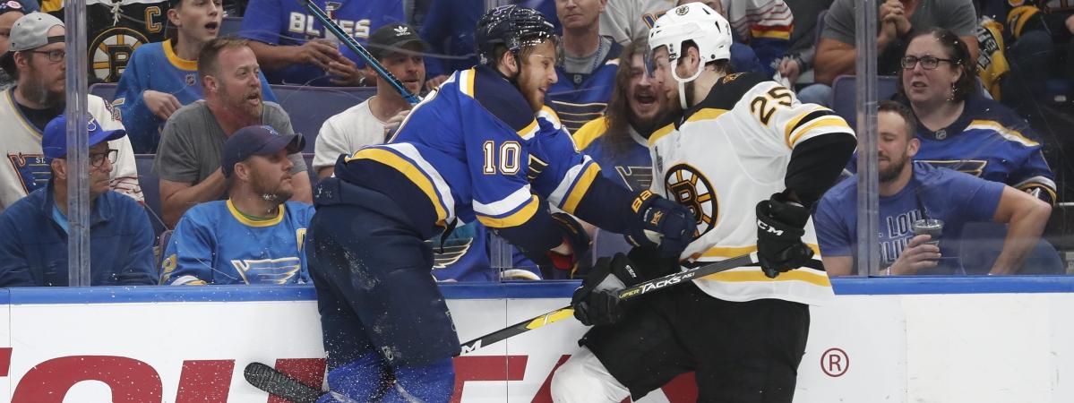 Blues center Brayden Schenn (10) and Bruins defenseman Brandon Carlo  battle along the board in Game 4 (Jeff Roberson)