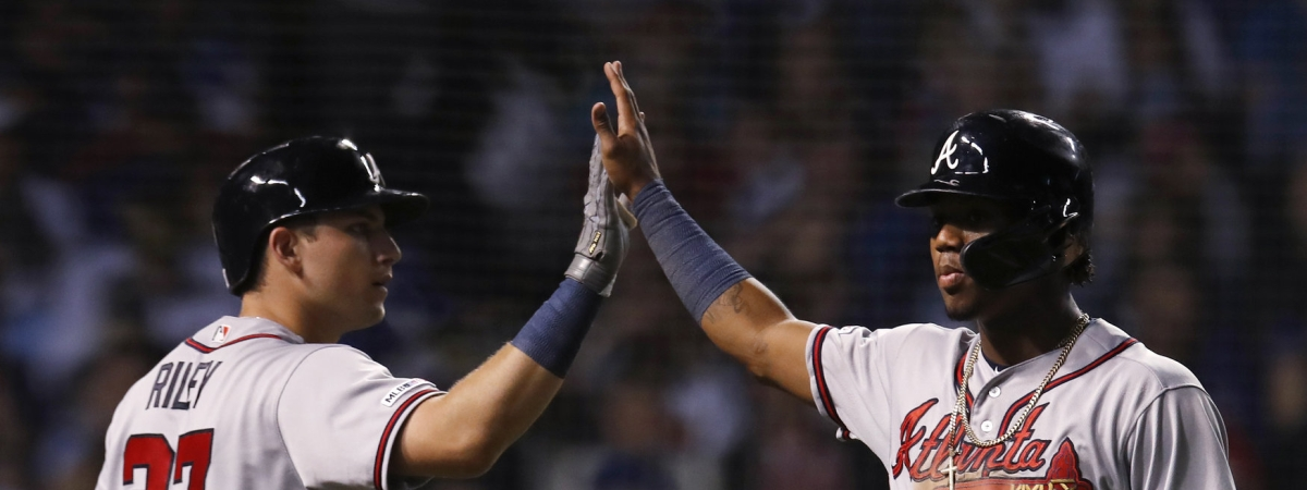 Braves' Ronald Acuna Jr. (right) high fives  with Austin Riley after scoring a run against the Cubs on June 24 (Jim Young)